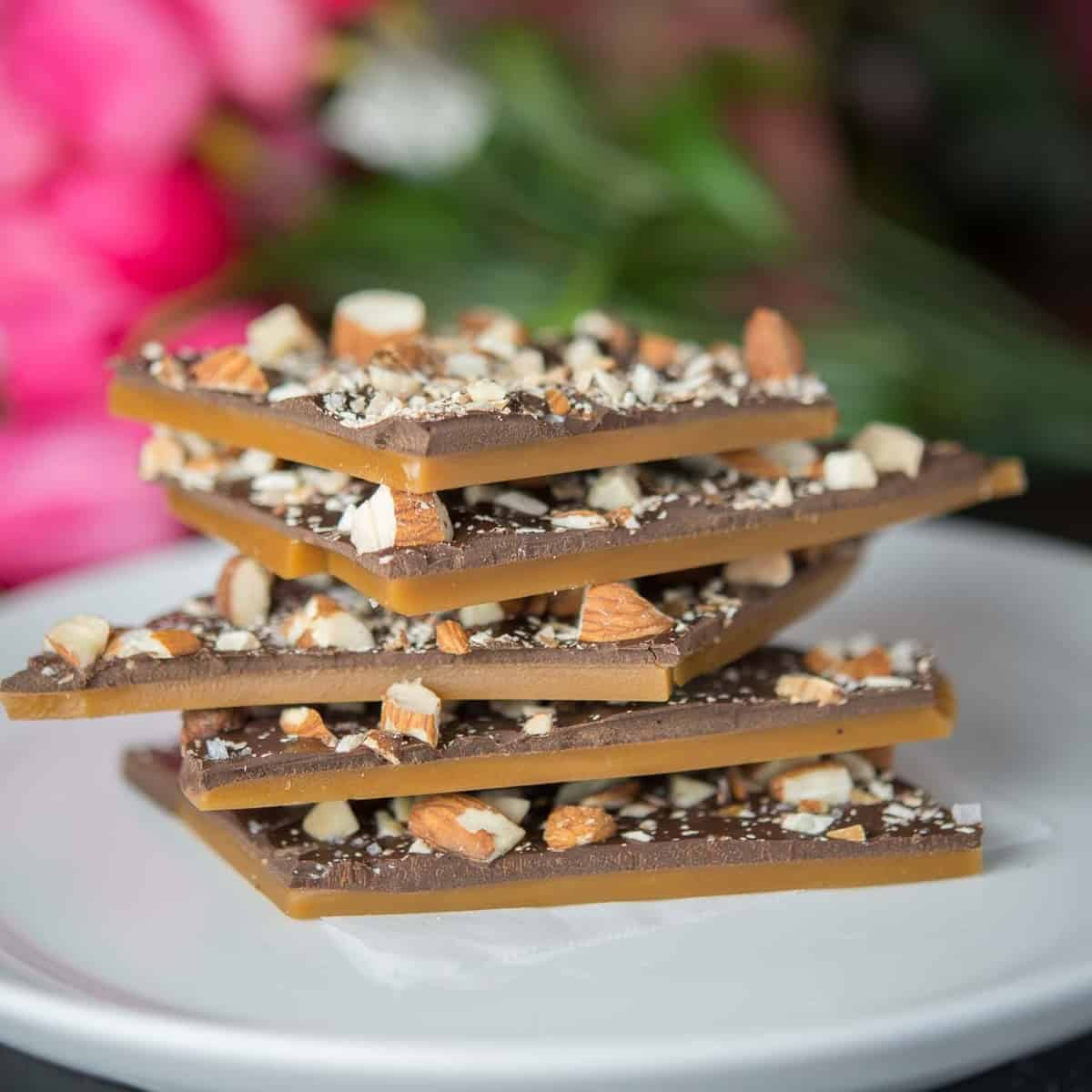 a stack of homemade butter toffee with a layer of dark chocolate and roasted almonds.