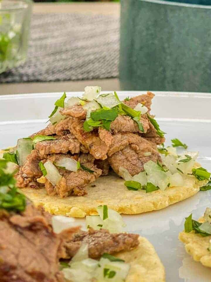 the best homemade carne asada meat on tacos with cilantro and onions