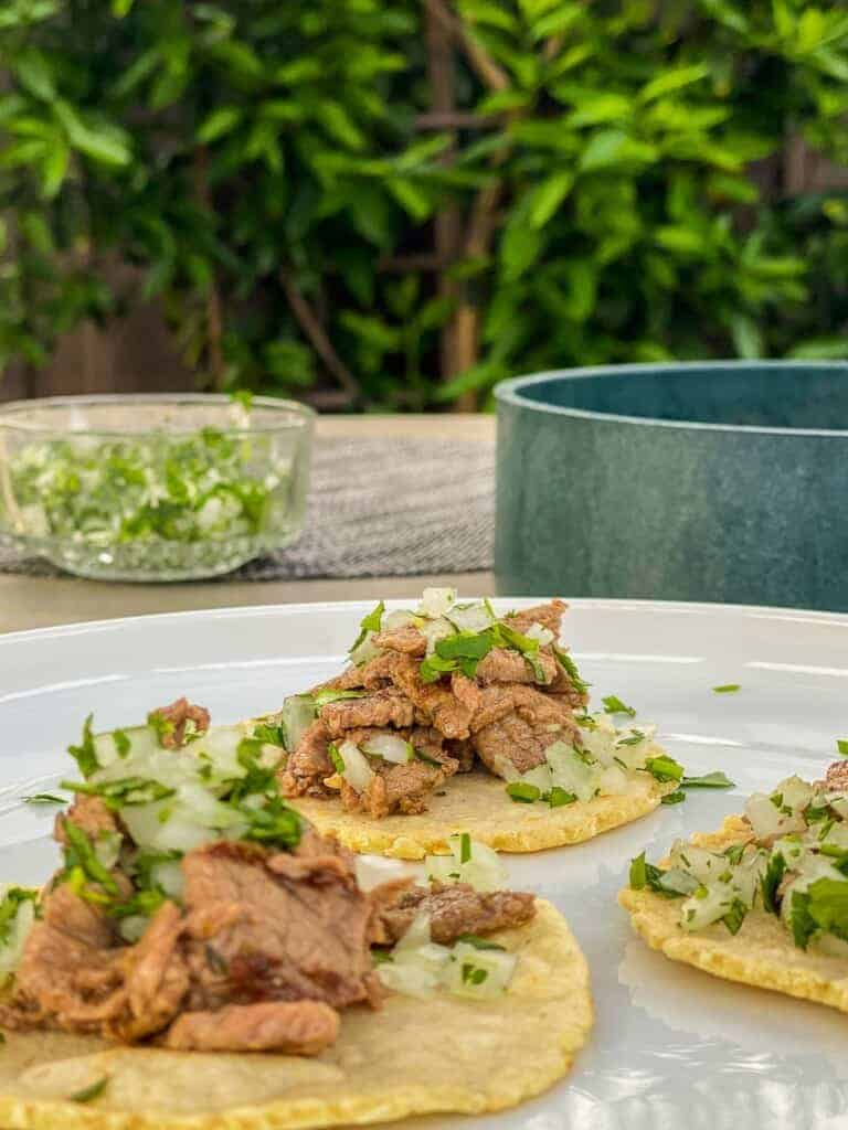 carne asada tacos served with cilantro and onions