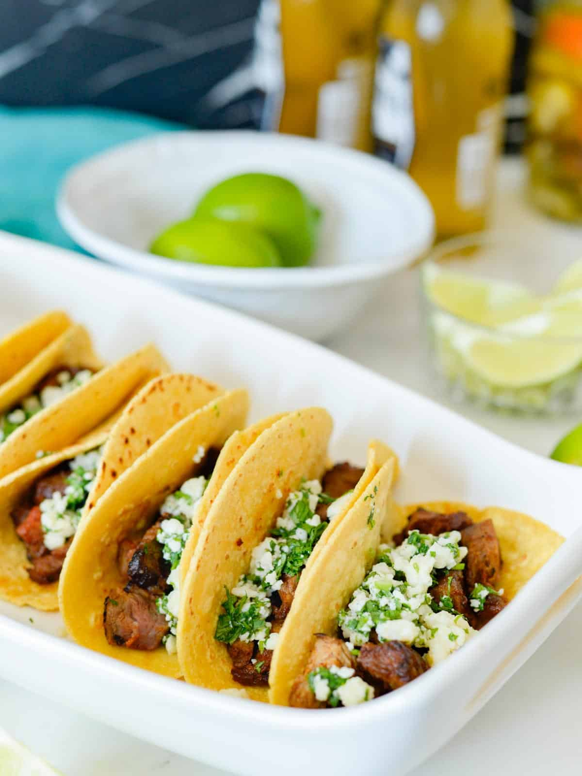carne asada tacos served at a cookout with fresh limes and cotija cheese