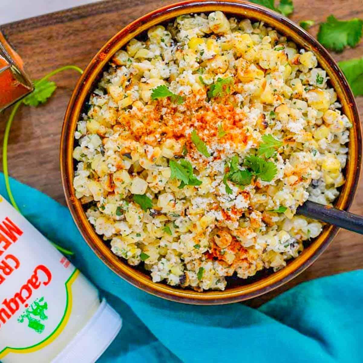 mexican corn salad recipe in a brown bowl with cilantro and crema