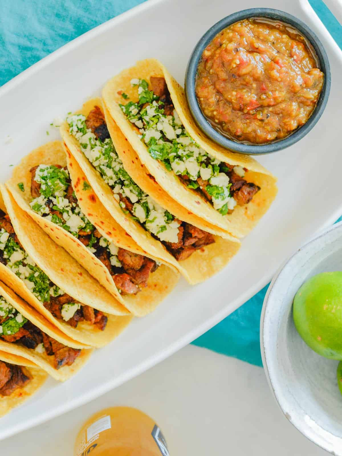 carne asada tacos with pepper sauce in a white platter