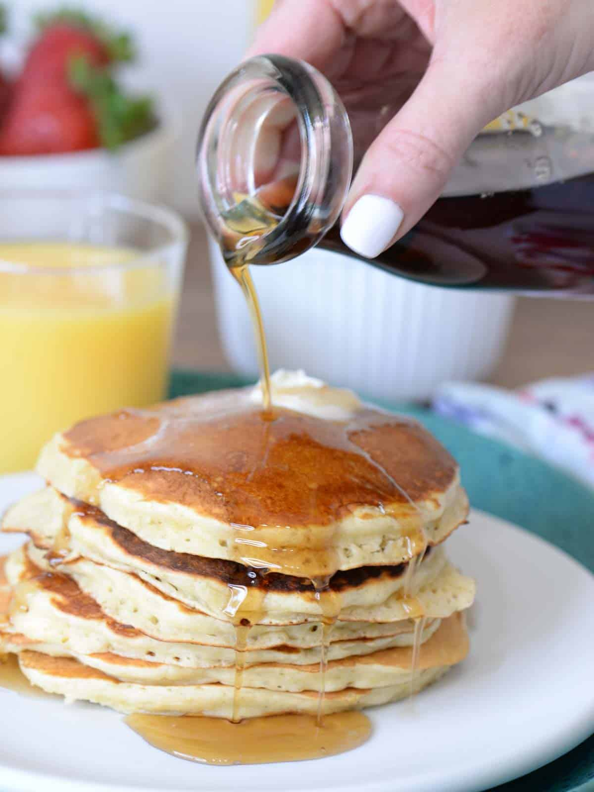 a stack of buttermilk pancakes with syrup being poured over