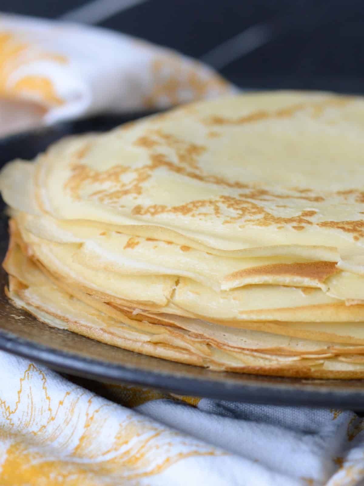 stack of homemade french crepes on a black plate