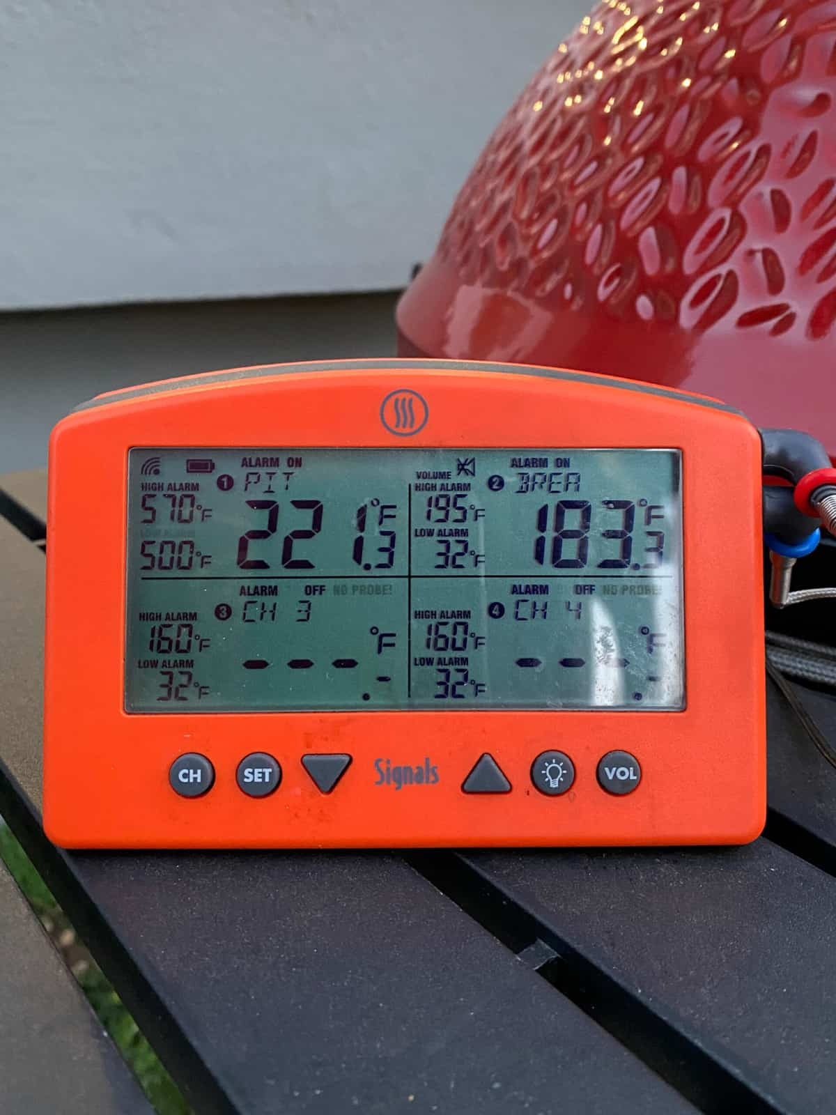 digital thermometer with 2 probes attached to monitor the grill temp and meat temp