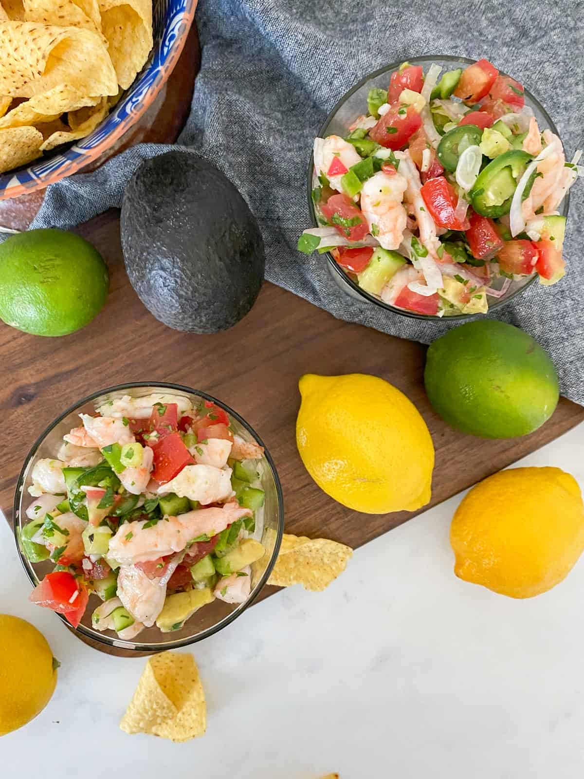 shrimp ceviche pictured with fresh lemons, limes, avocados, and tortilla chips