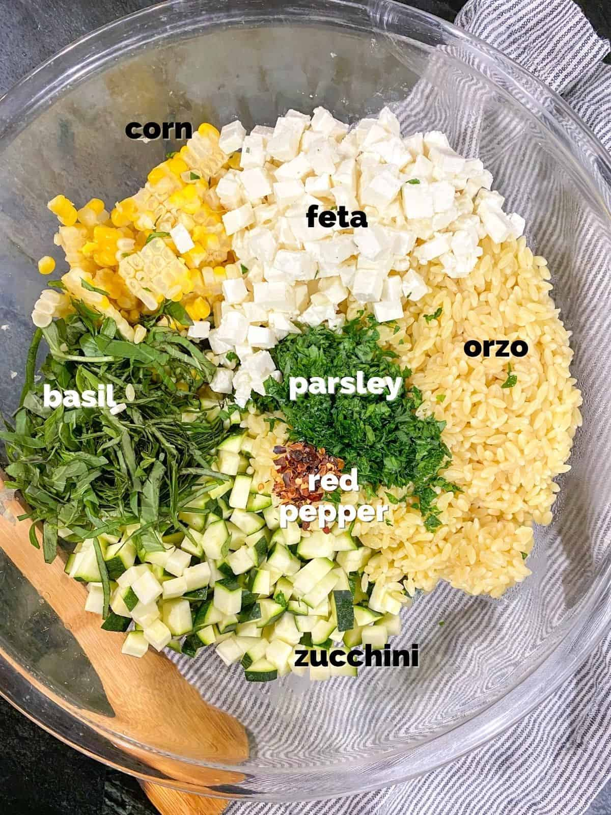 ingredients for the orzo salad with feta in a bowl ready to be tossed together