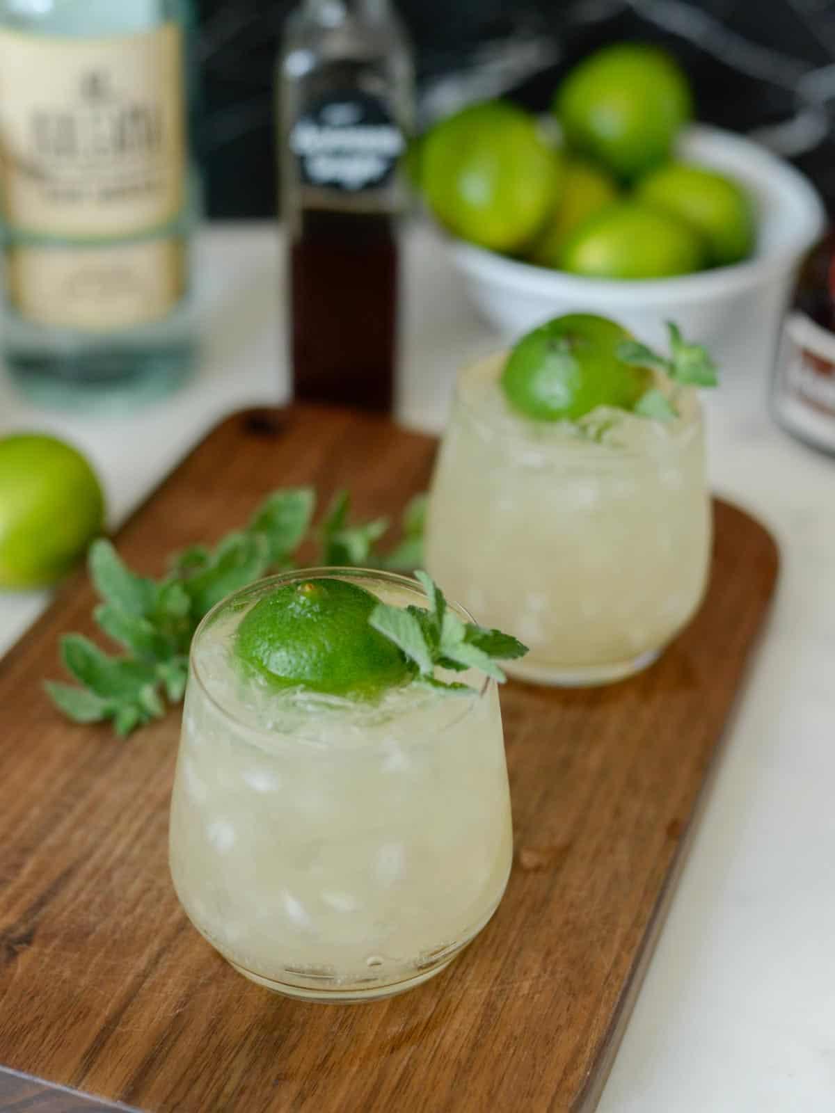 mai tais on a table with fresh limes