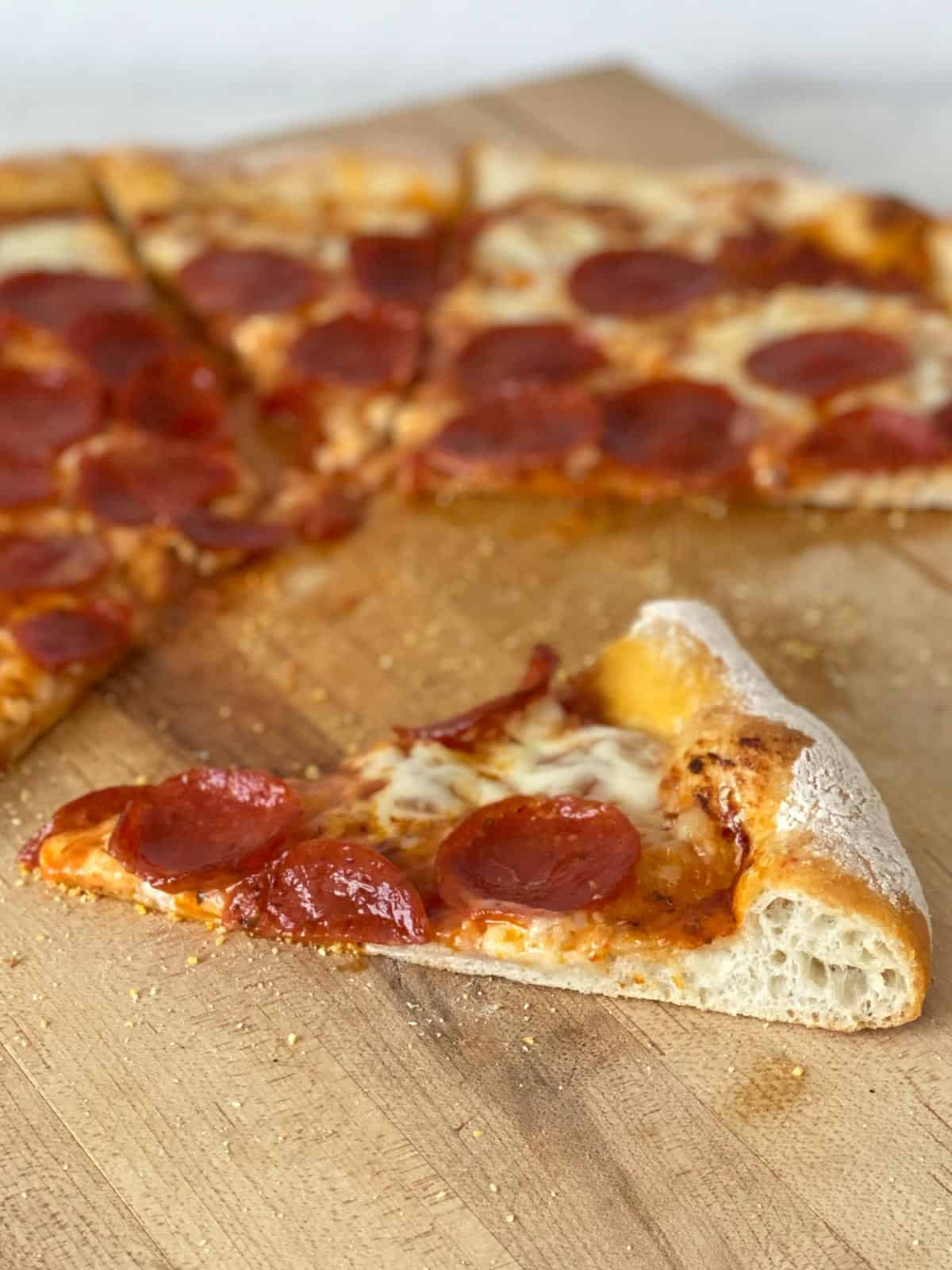 slice of homemade pizza crust topped with cheese and pepperoni
