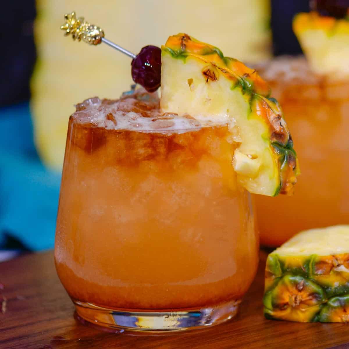 Hawaiian mait tai cocktail garnished with a pineapple wedge and a maraschino cherry